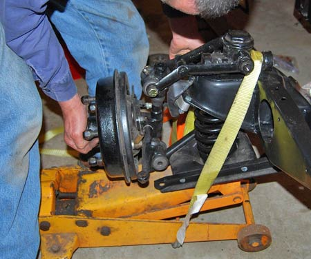 The tie-down strap around the jack holds the A arms and coil spring safely in their proper positions so mechanic Vince Sauberlich can position the lower end of the spindle and put a new pin through the bolt hole in the lower A arm.