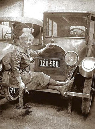 Mechanic Helen J. Owens knew how to put a sturdy front bumper to good use as a mechanic's stool. The car wears 1918 New York license plates.